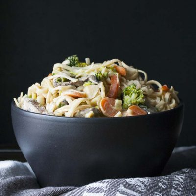 Black bowl filled with noodles and veggies covered in peanut sauce
