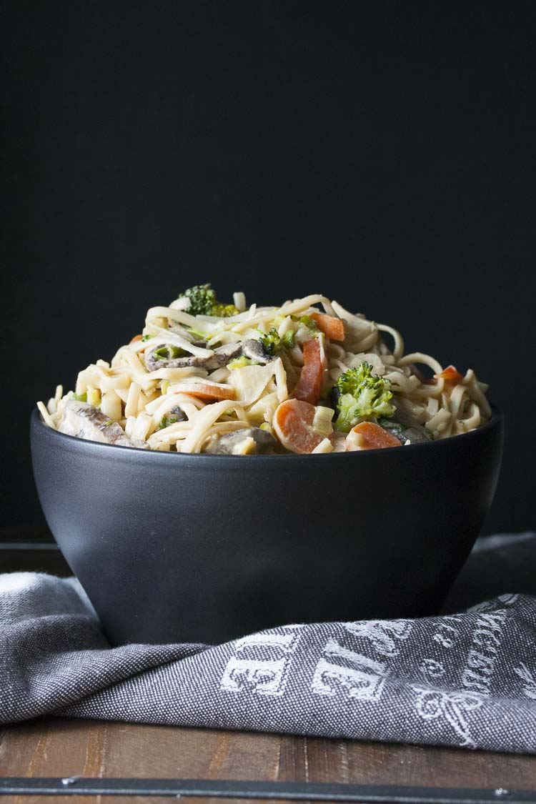 Noodles tossed in peanut sauce and veggies in a black bowl