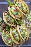 Top view of fully loaded crispy vegan tacos on a wooden table