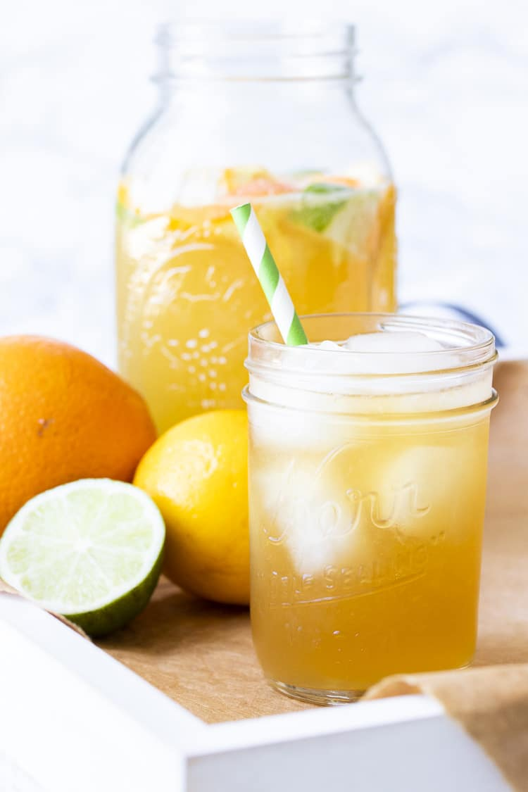 White tray with sparkling citrus tea over ice next to citrus fruit