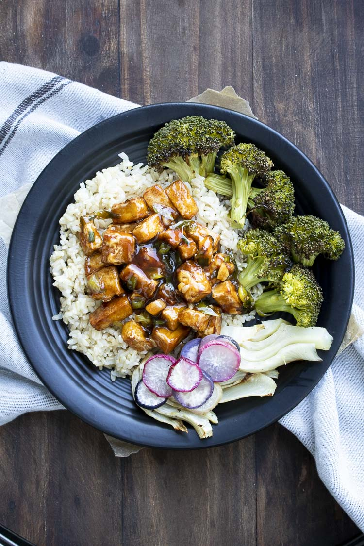 Black plate with General Tso's tofu, roasted broccoli, fennel, and roasted radishes on top of brown rice