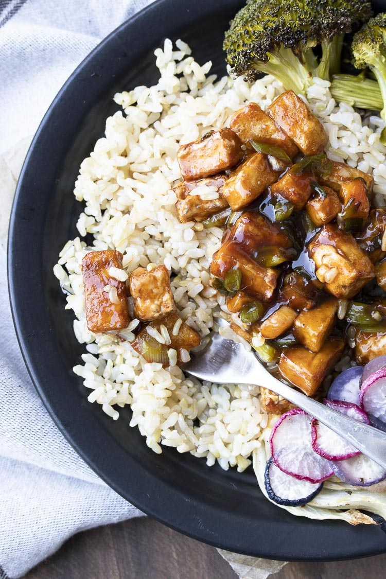 Close up of fork in brown rice with General Tso's tofu