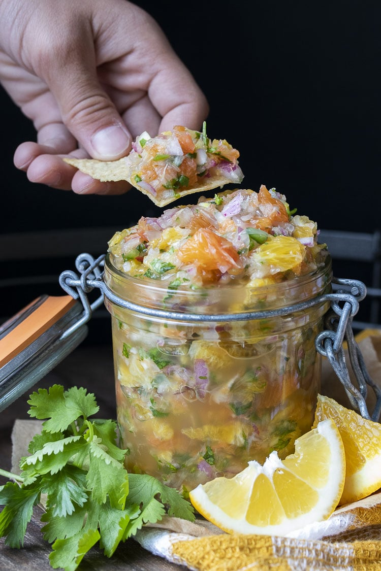 Hand dipping a chip into a glass jar filled with fresh citrus salsa