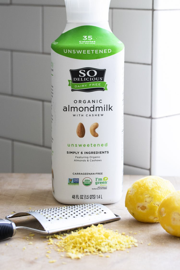 Bottle of So Delicious almondmilk with cashew next to grated lemon zest