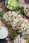 Top view of roasted veggie tacos surrounded by bowls of toppings