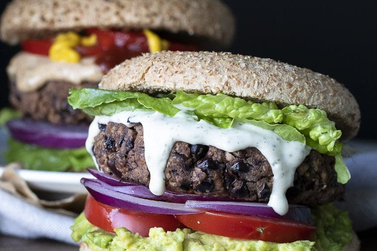 Black bean burger topped with lettuce, ranch dressing, red onions, tomato and avocado
