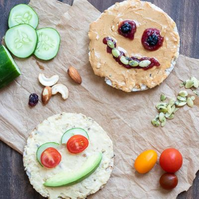 Rice cakes decorated as faces using nut butter, hummus, seeds, veggies, dried fruit and nuts