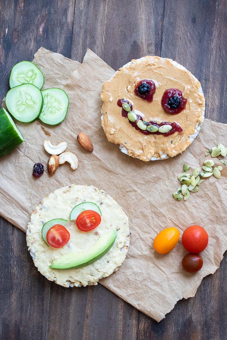 Rice cakes with faces made from peanut butter, hummus, dried fruit, nuts, seeds and veggies