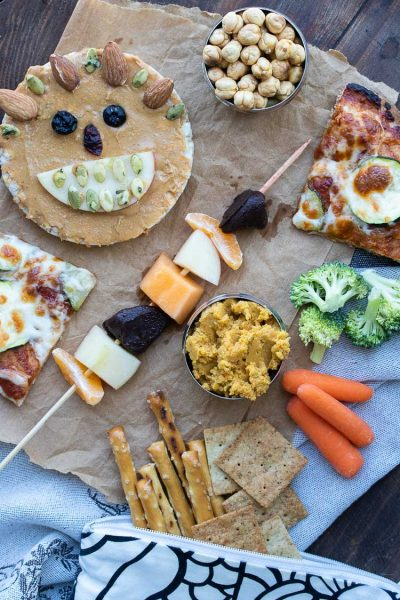 A variety of school lunch items like fruit kebabs, pizza, hummus, veggies and pretzels