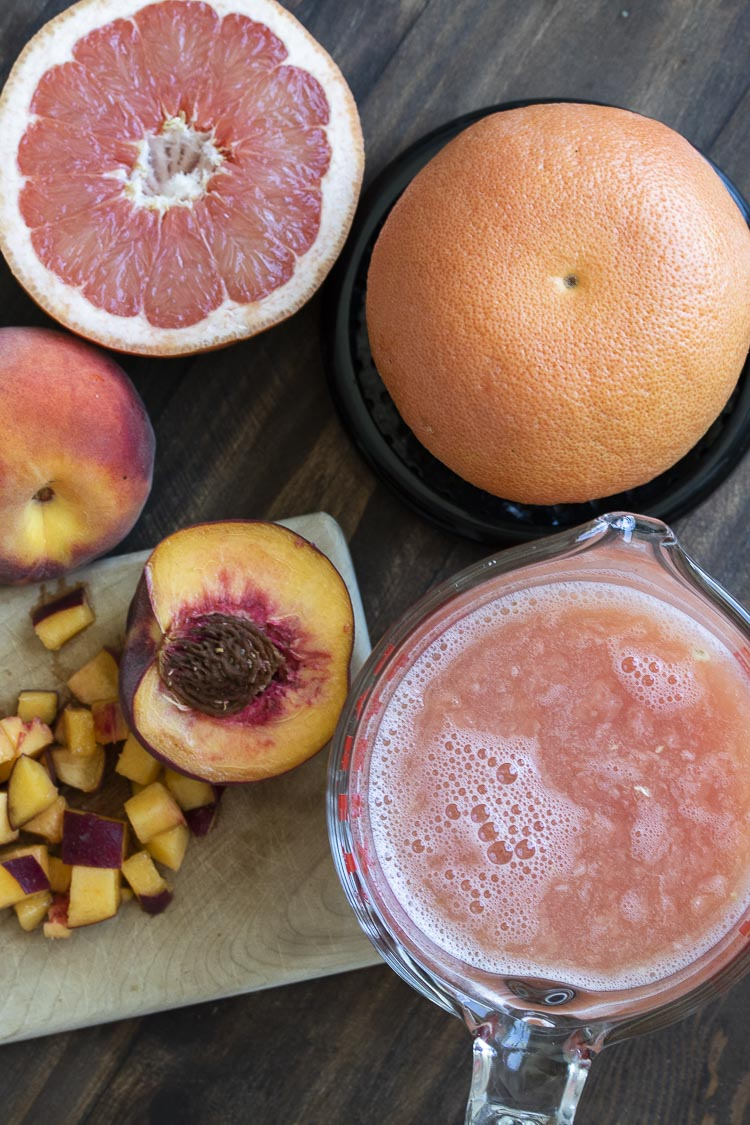 Top view of chopped peaches and fresh grapefruit being juiced