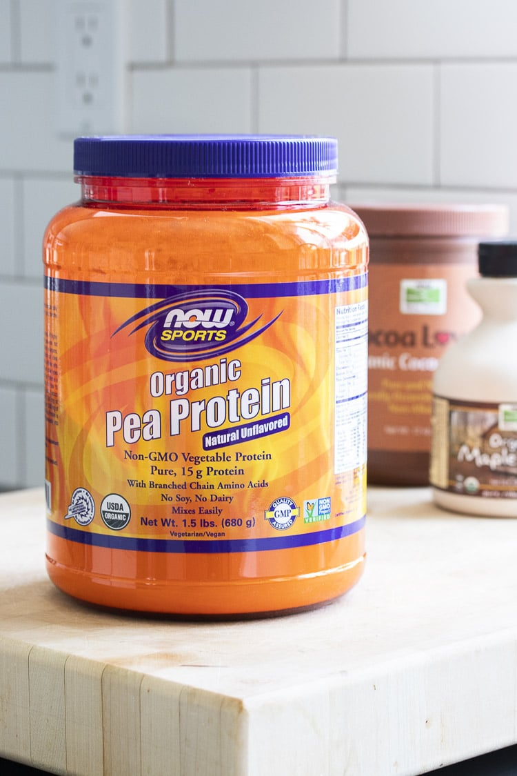 Orange NOW Sports pea protein powder container on a wood table
