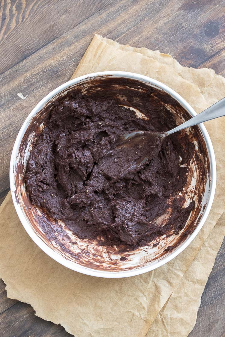 Spoon mixing brownie batter in a white bowl
