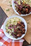Top view of two white bowls with quinoa, cabbage slaw and BBQ cauliflower bites