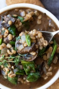 Metal spoon scooping out some barley, mushroom and spinach stew