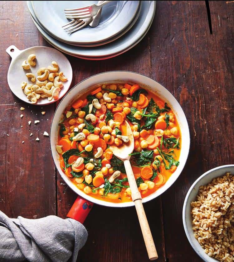 White bowl filled with red curry made of chickpeas, carrots, cashews and spinach