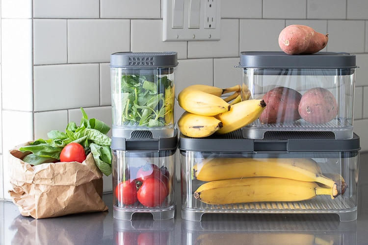 Plastic containers filled with fruit and veggies sitting on grey countertop