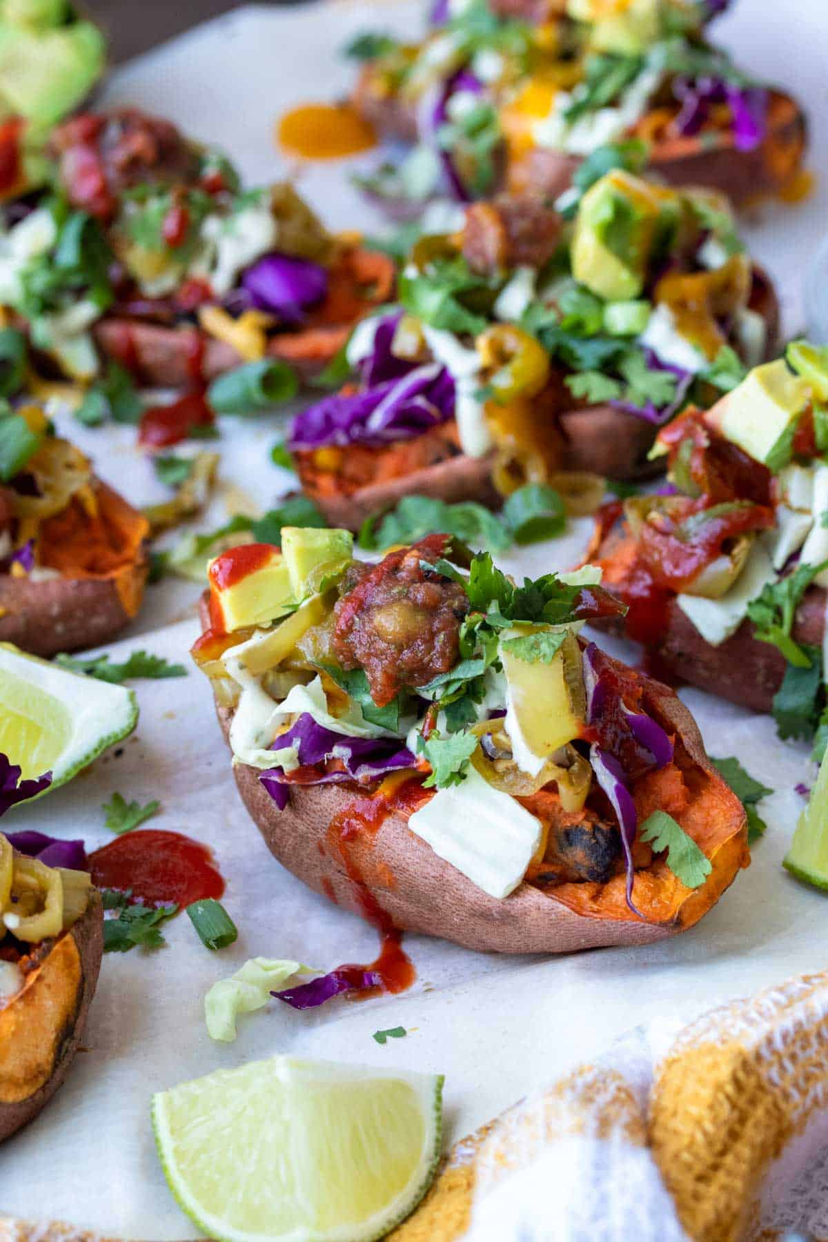 Front view of baked sweet potato skin loaded with toppings on white parchment