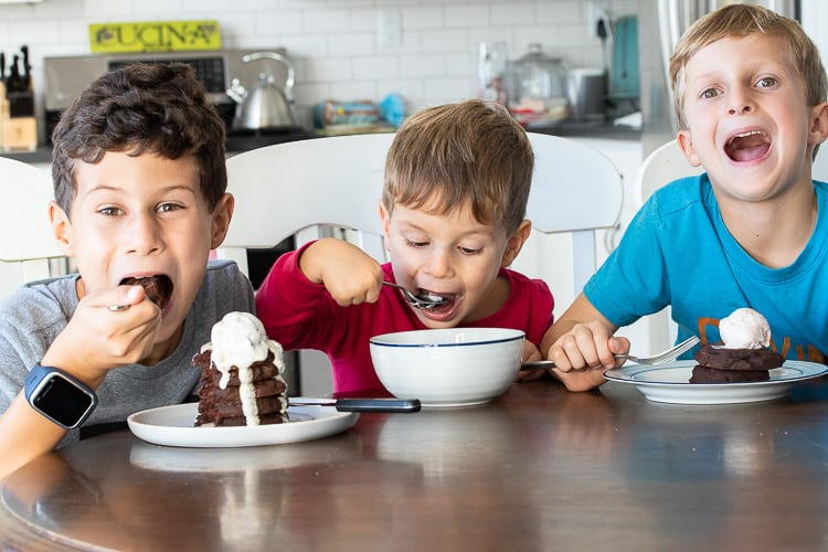 Three young boys eating chocolate pancakes and ice cream at a wooden table