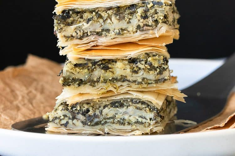 Pile of three pieces of spanakopita on a white plate