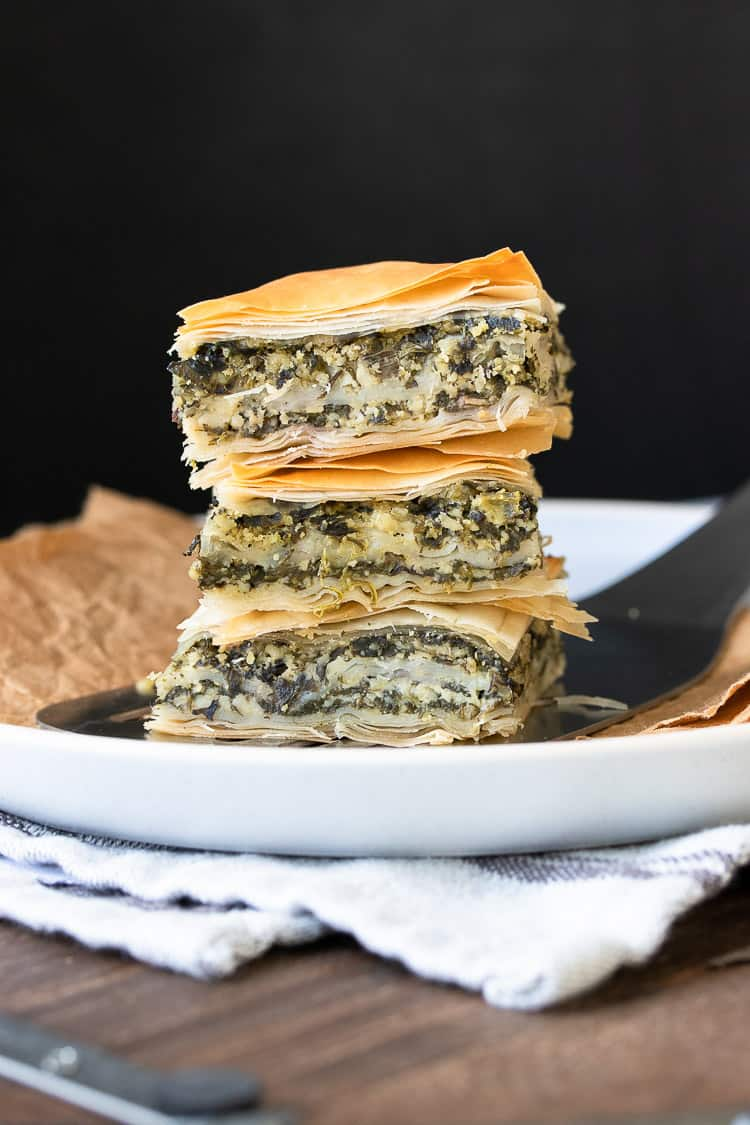 Three pieces of vegan Greek spanakopita piled on top of each other