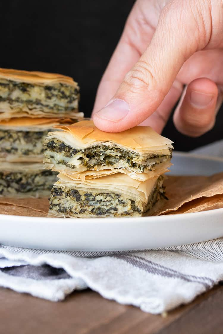 Hand picking up a piece of spanakopita with a bite out of it