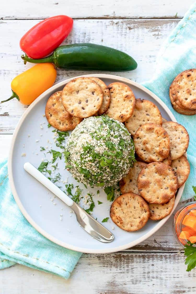 Top view of cheese ball on a grey plate surrounded by crackers, peppers and carrot sticks
