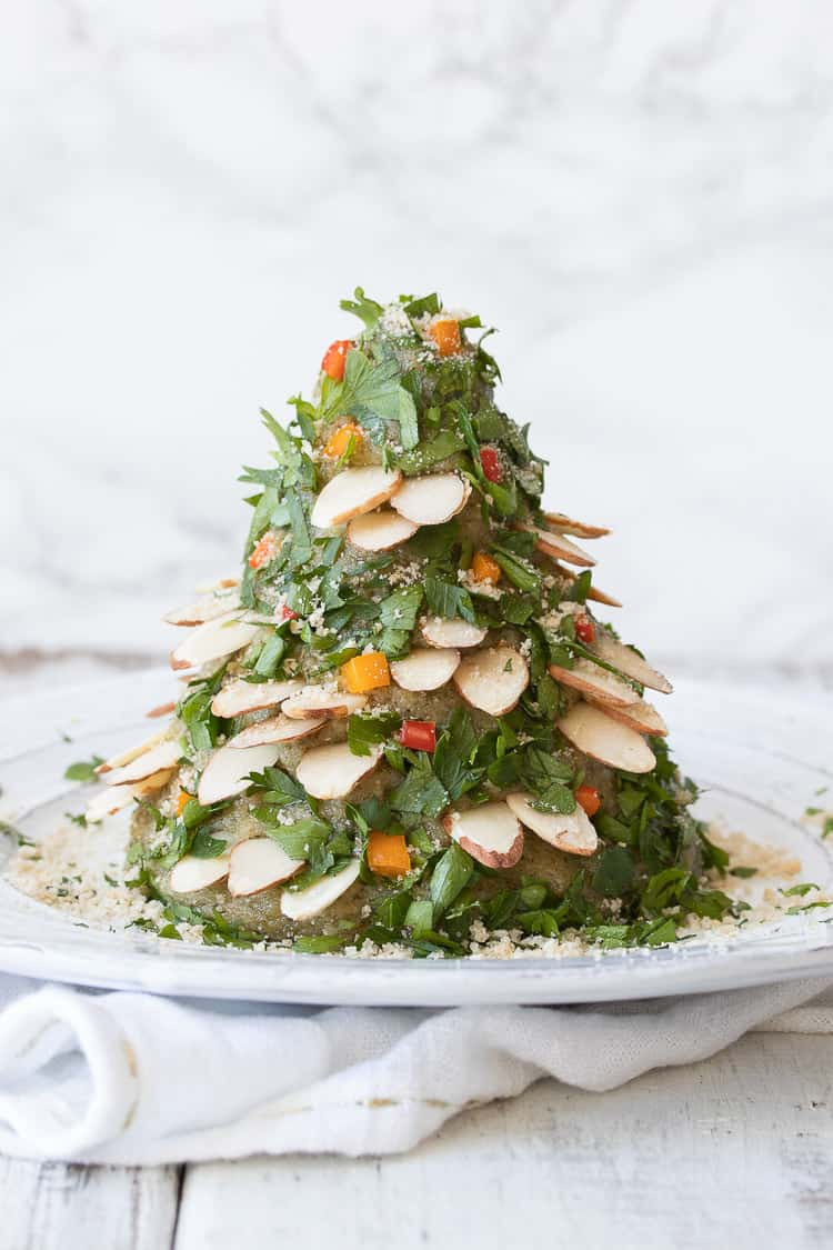Cheese ball decorated like a Christmas tree with chopped herbs, veggies and slivered almonds