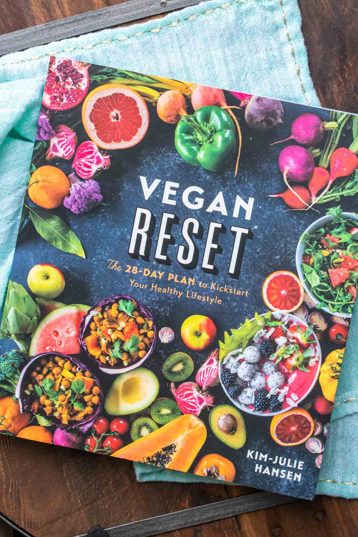 Cover of a vegan cookbook with veggies and fruits on the front