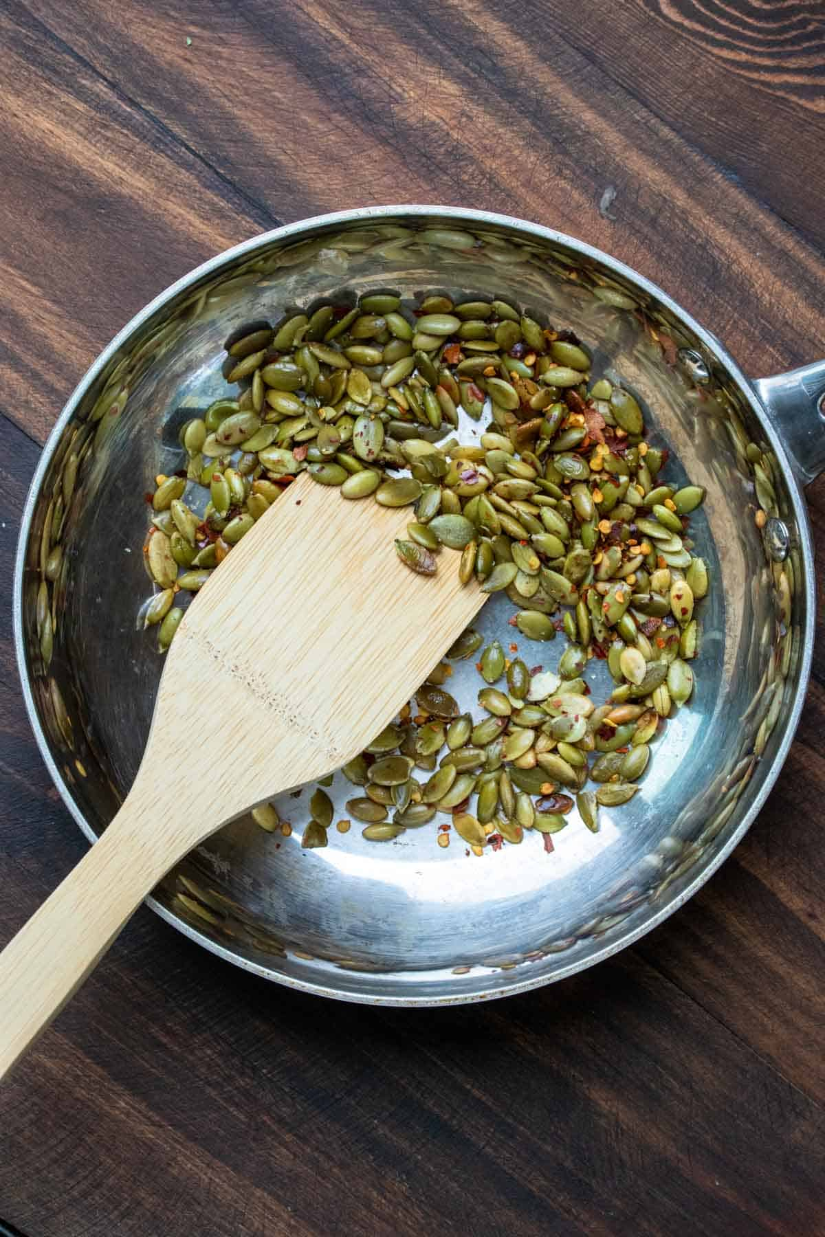 Pumpkin seeds and spices cooking in a pan