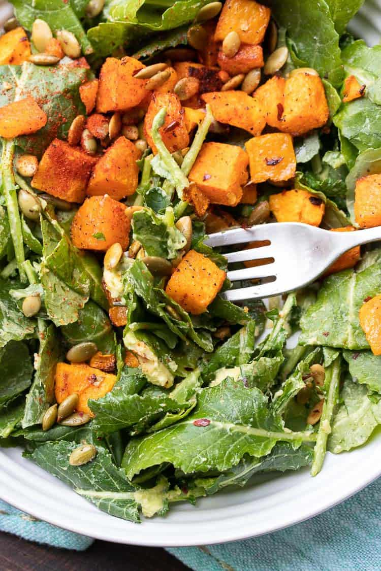 Fork taking a bite of an avocado kale salad with butternut squash pieces