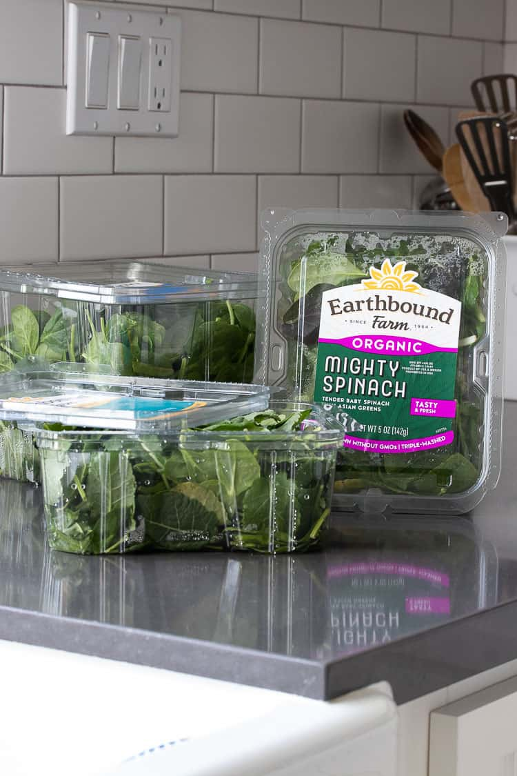 Plastic containers of Earthbound Farm Organic greens on kitchen counter