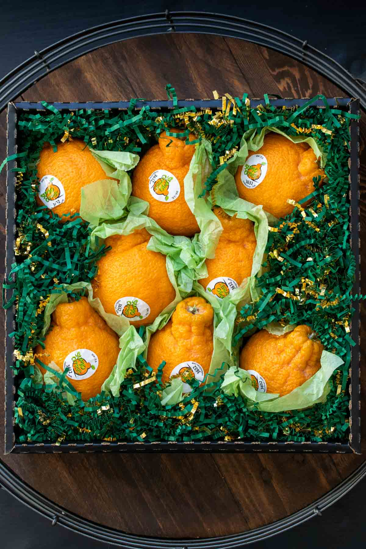 Oranges in box filled with green paper grass shreds