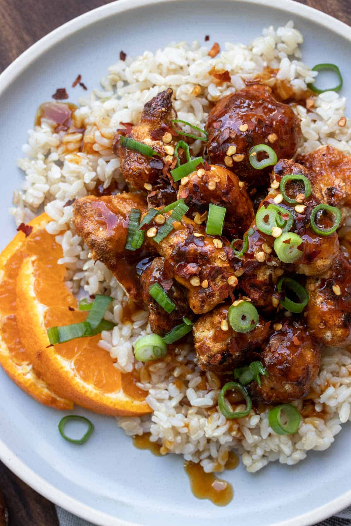 Close up of crispy cauliflower tossed in Chinese orange sauce over rice