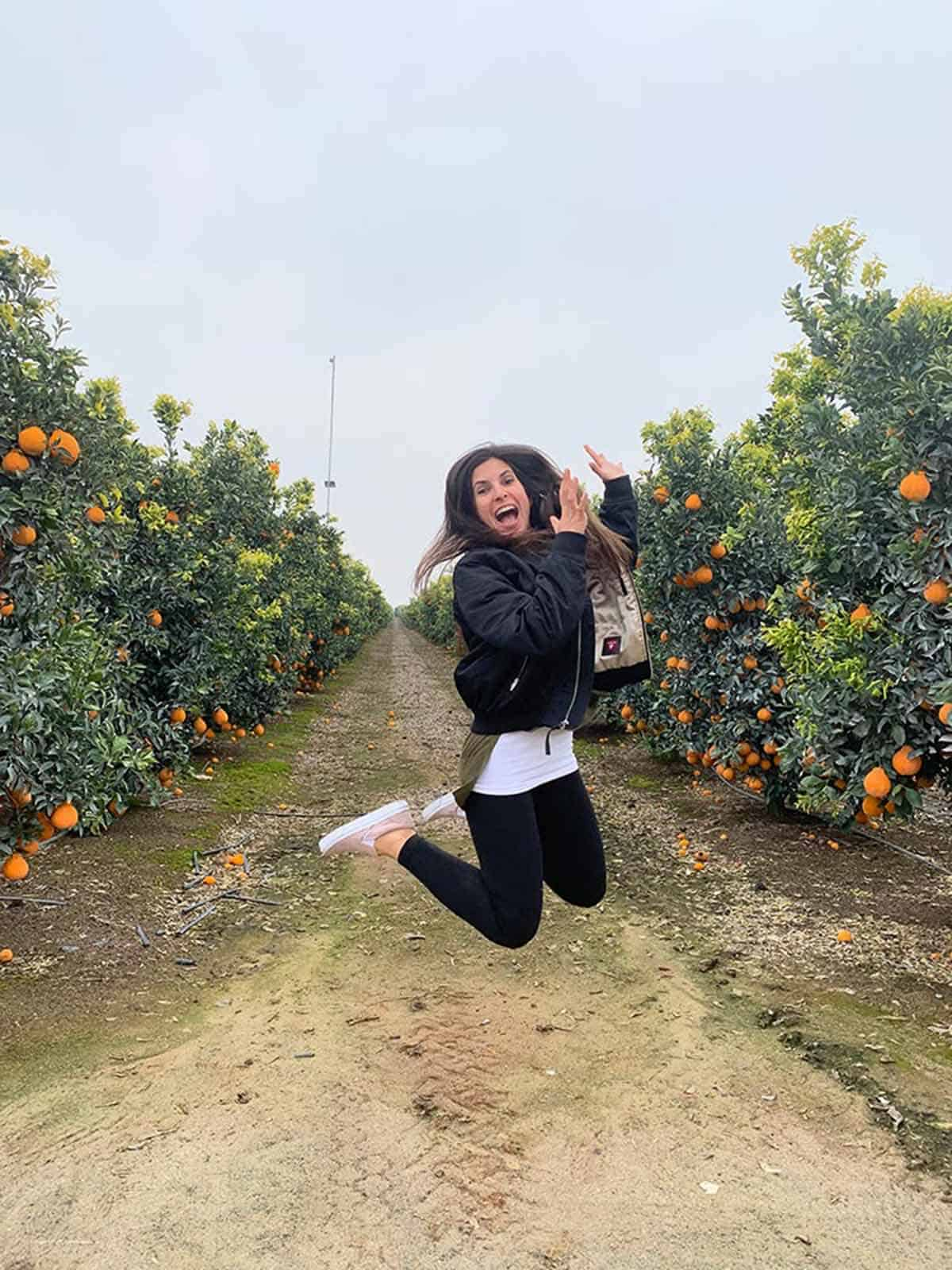Woman jumping in the air in between two lines of citrus trees