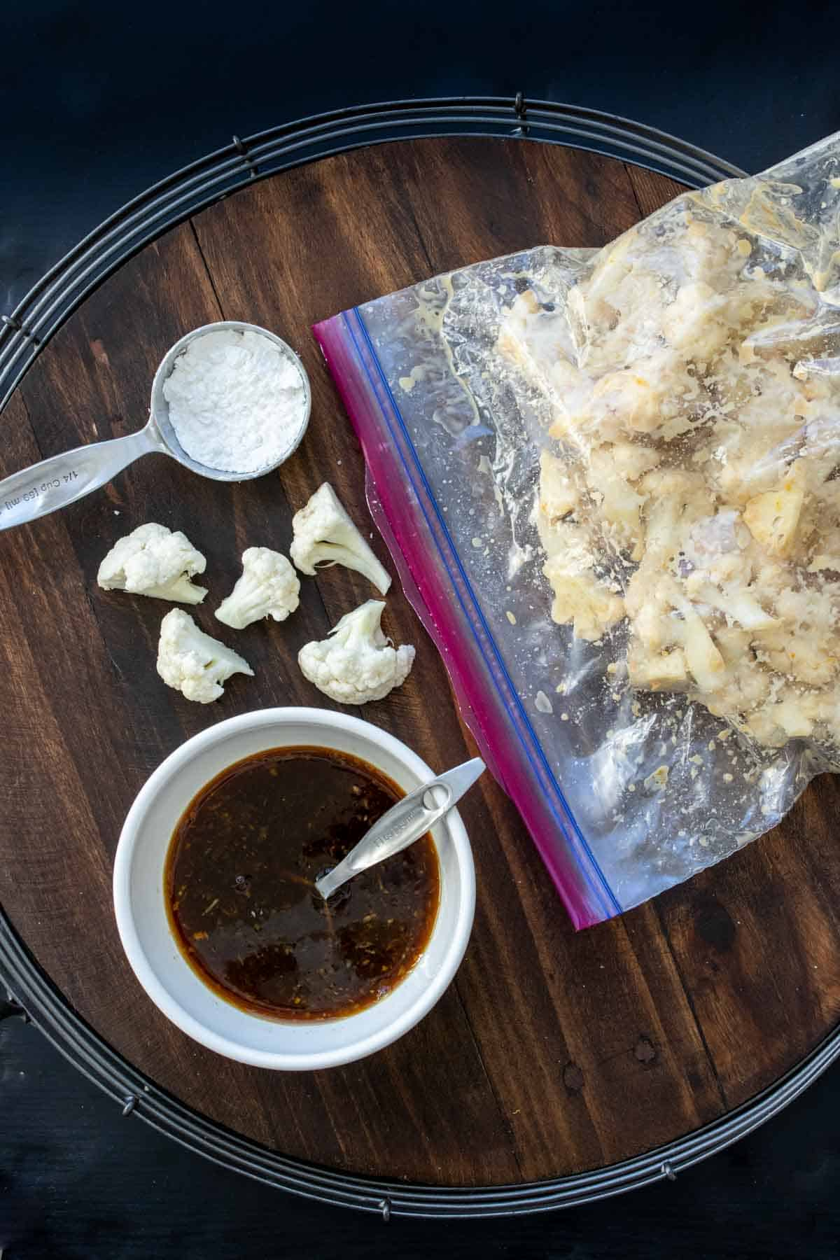 Plastic bag filled with cauliflower pieces next to bowl with brown sauce