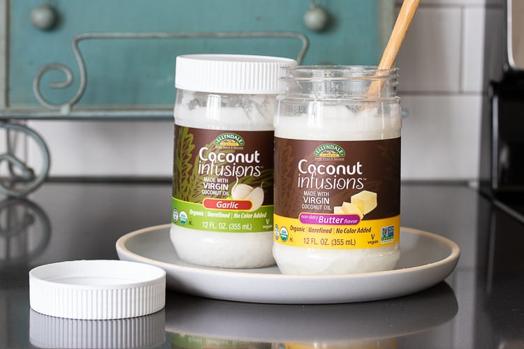 Two jars of coconut oil on a white plate on the kitchen counter