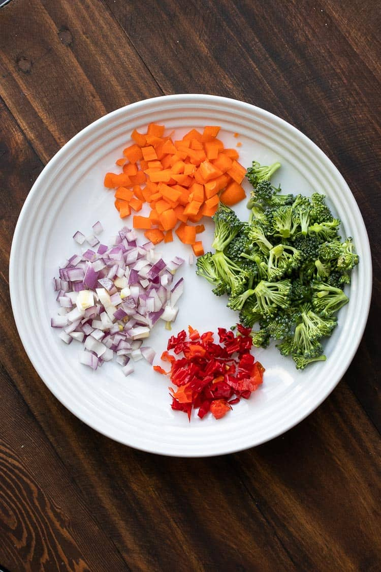 White plate with chopped carrots, broccoli, red peppers and red onions