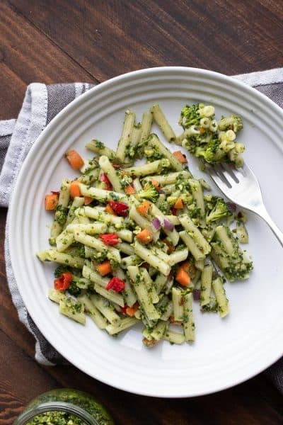 Vegan pesto pasta and veggies and a fork on a white plate