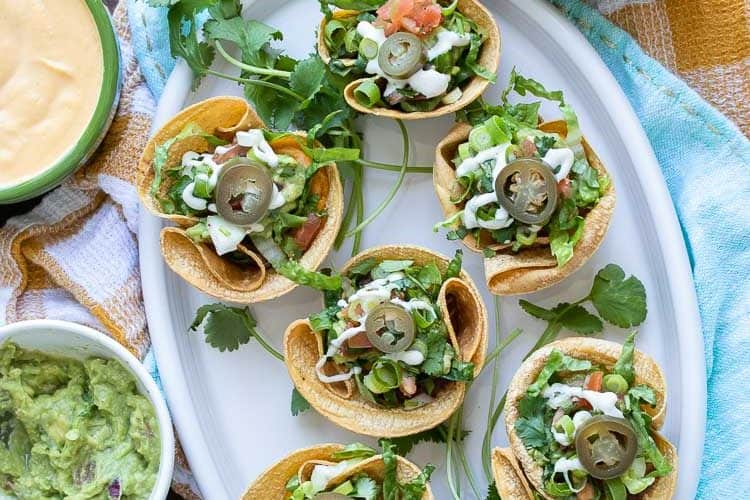 Top view of crunchy taco cups filled with toppings on a white platter