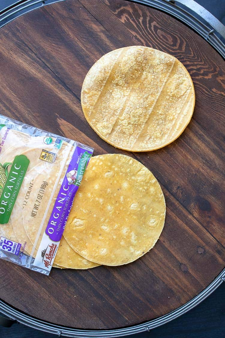 Tortillas coming out of a package laying on a wood tray