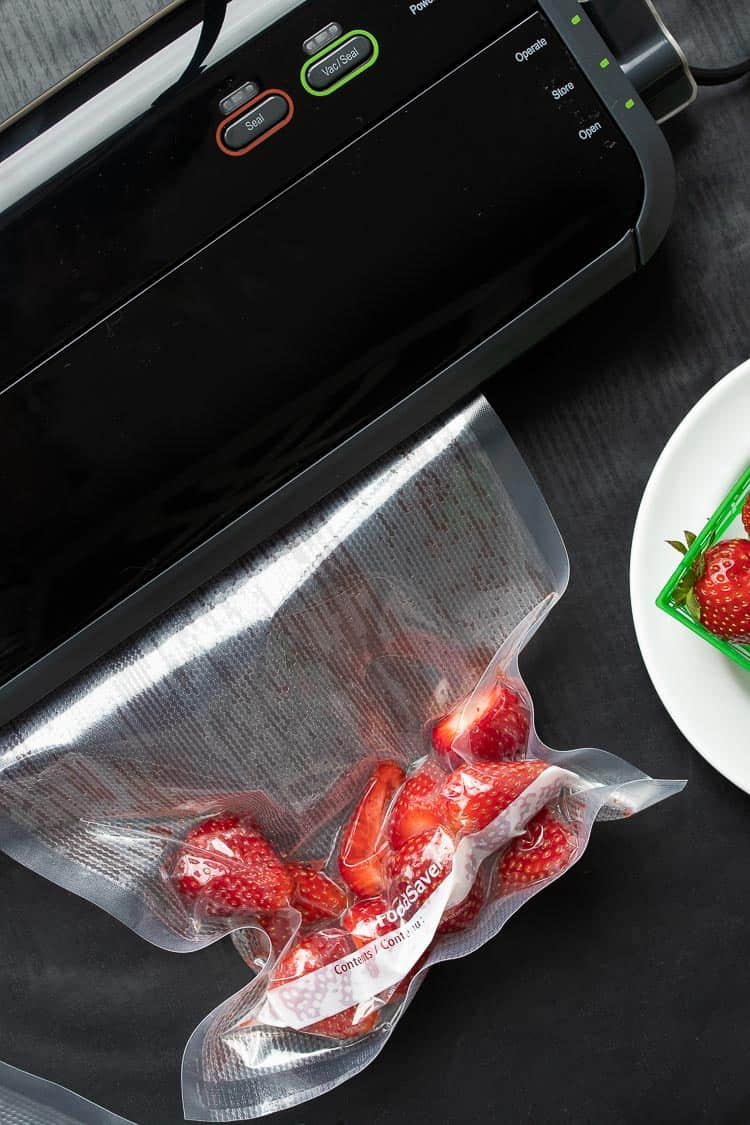 Fresh strawberries being sealed in a vacuum seal bag by a Foodsaver machine