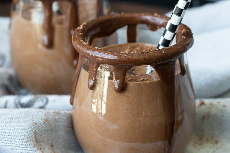 Glass jars rimmed with melted chocolate filled with a chocolate smoothie