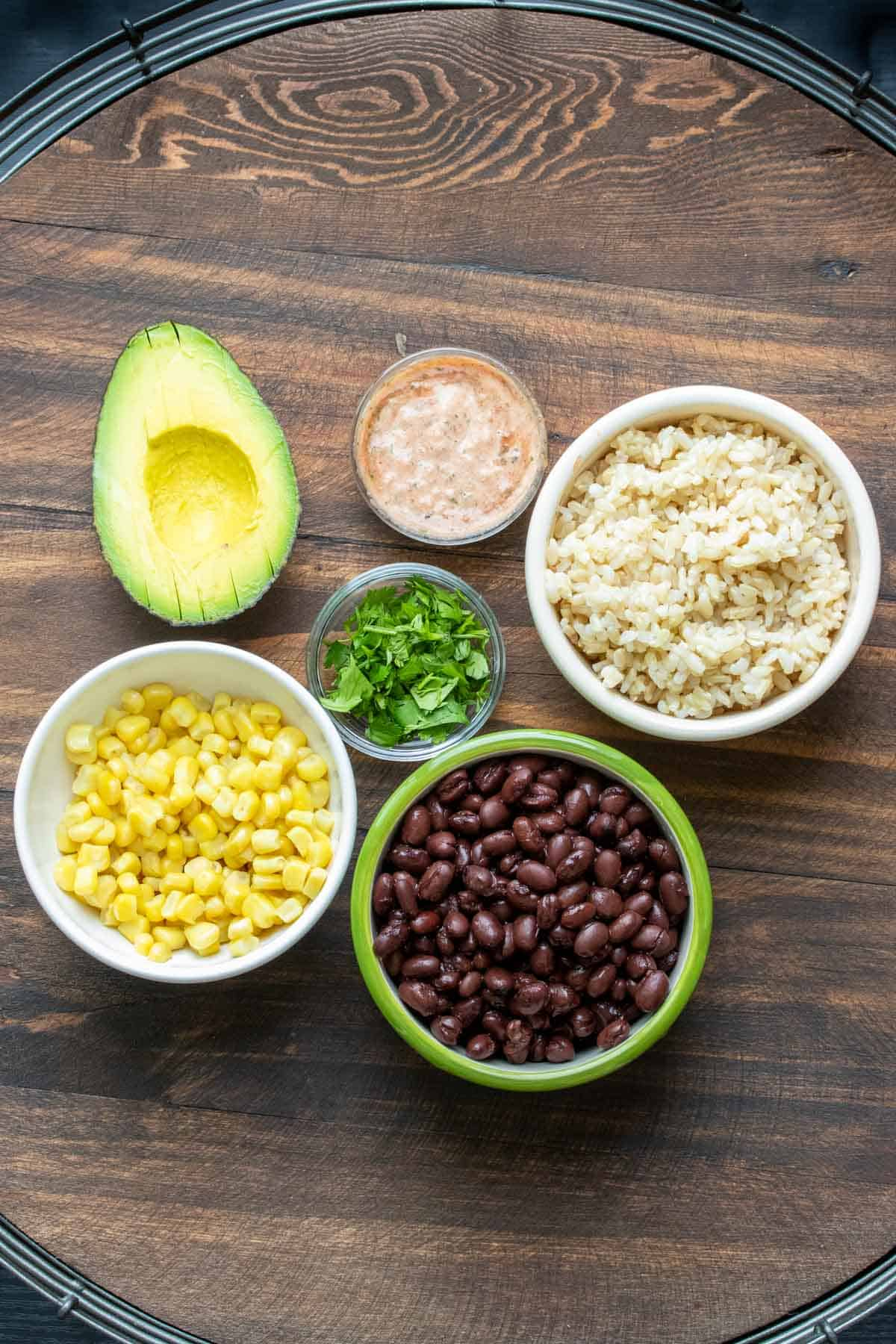 Beans, corn, rice, cilantro, creamy red sauce and half an avocado on a wooden table