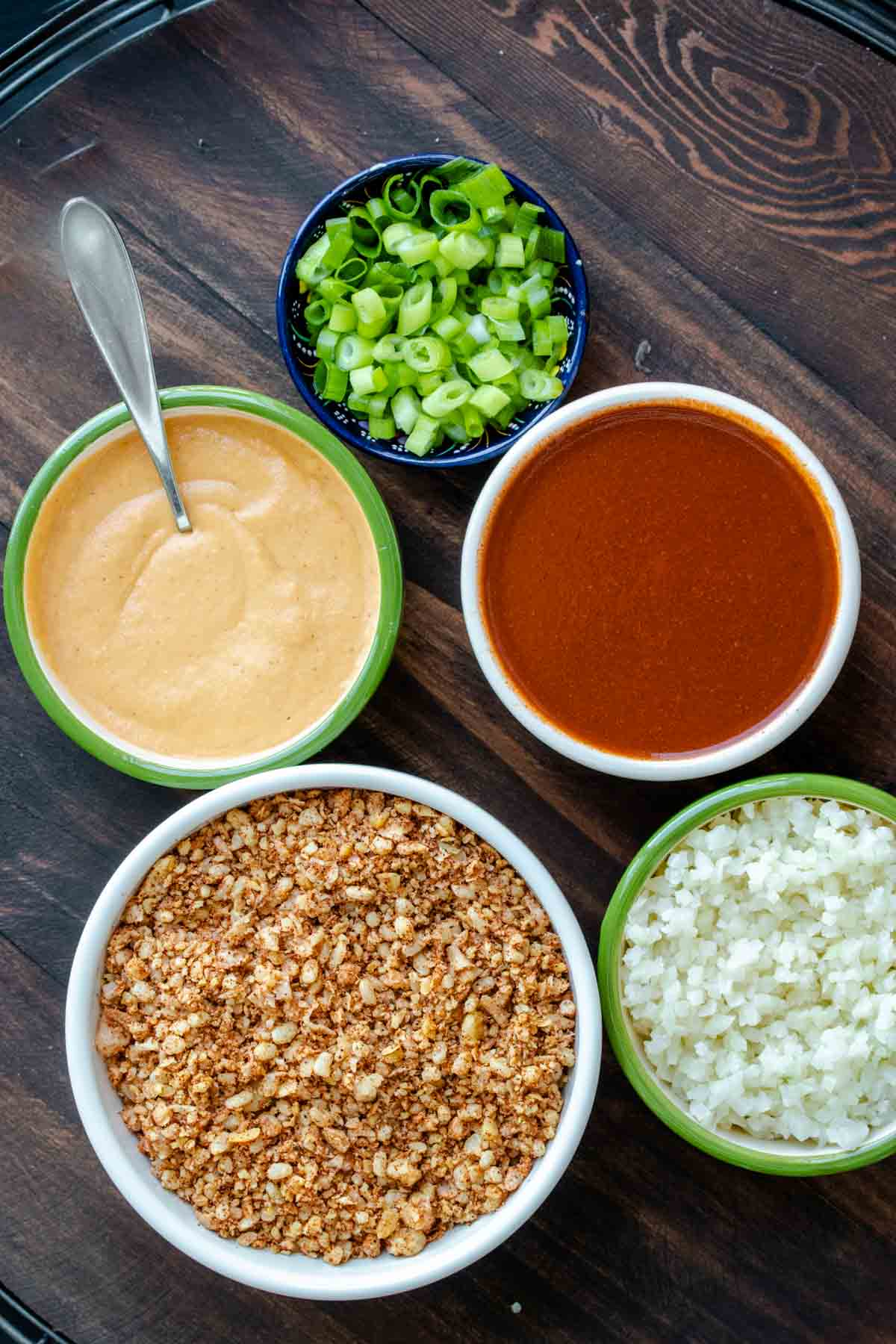 Bowls with vegan taco meat, cheese sauce, cauliflower rice, enchilada sauce and green onions