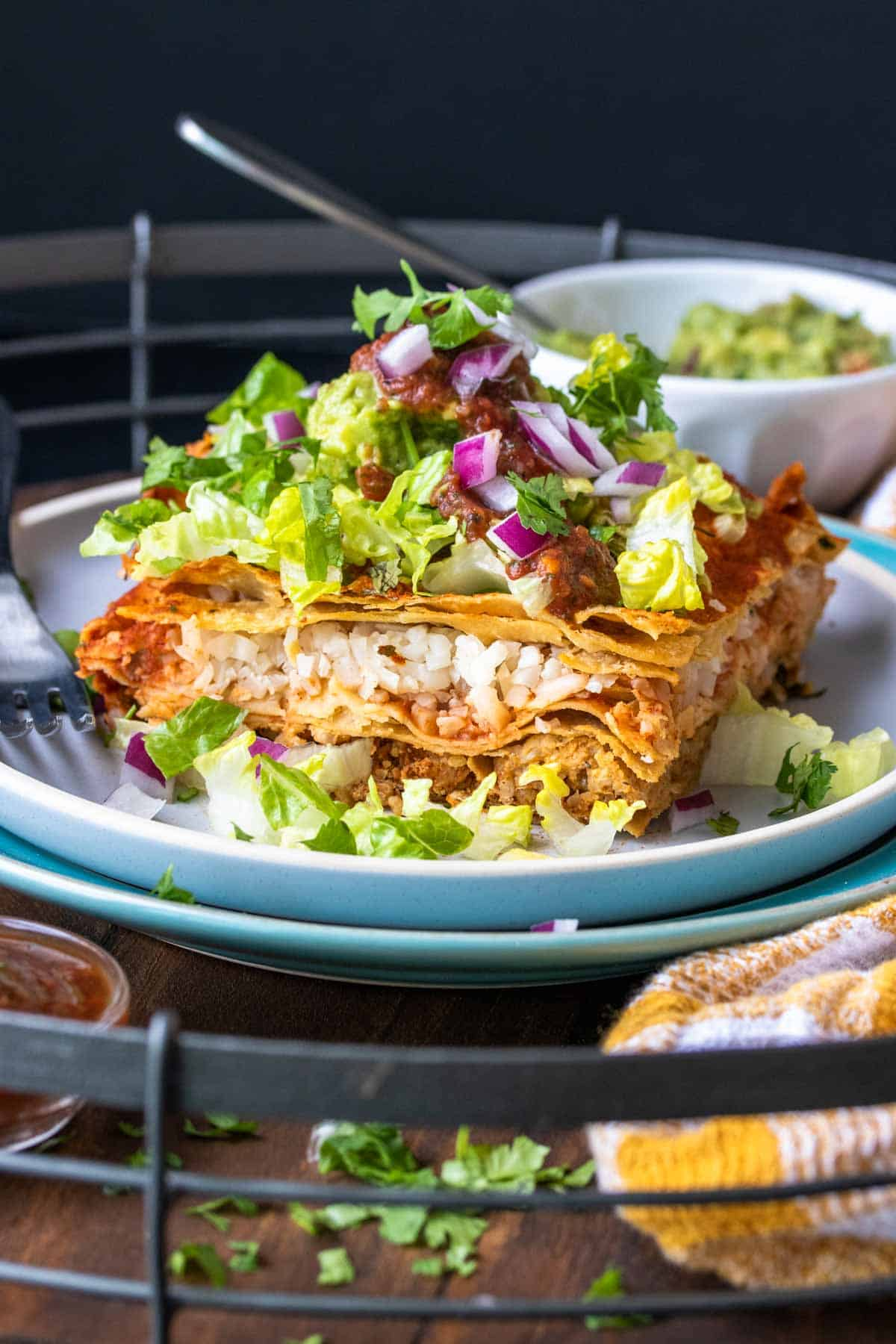 Piece of enchilada casserole topped with lettuce and red onions on a white plate