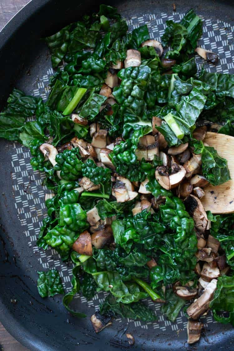 Spoon sautéing kale and mushrooms in a pan