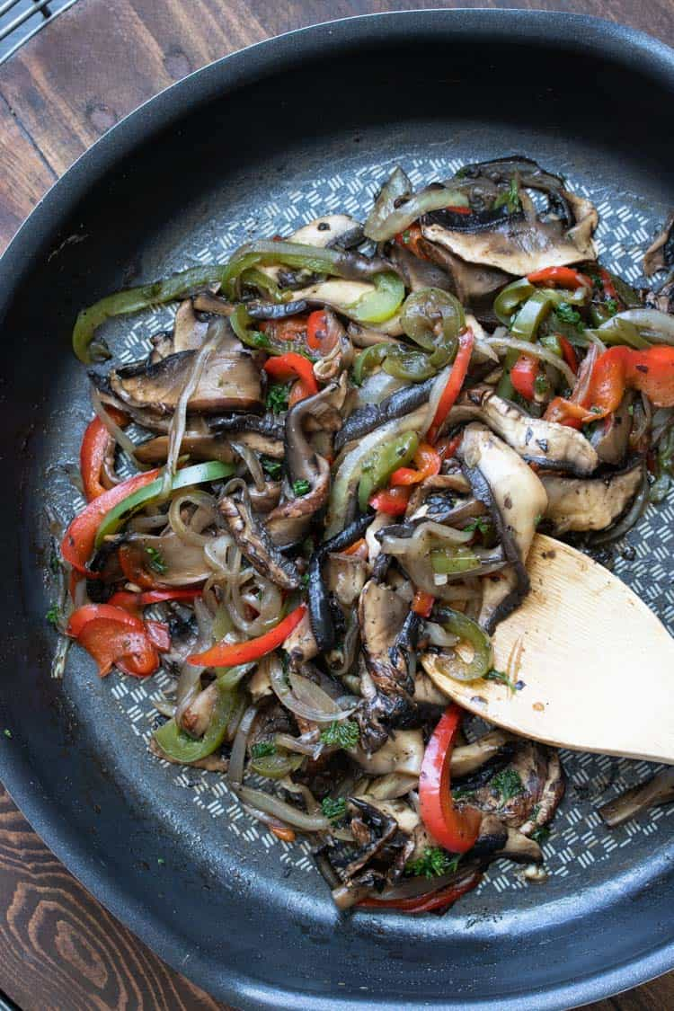 Wooden spoon sautéing mushrooms and peppers in a frying pan