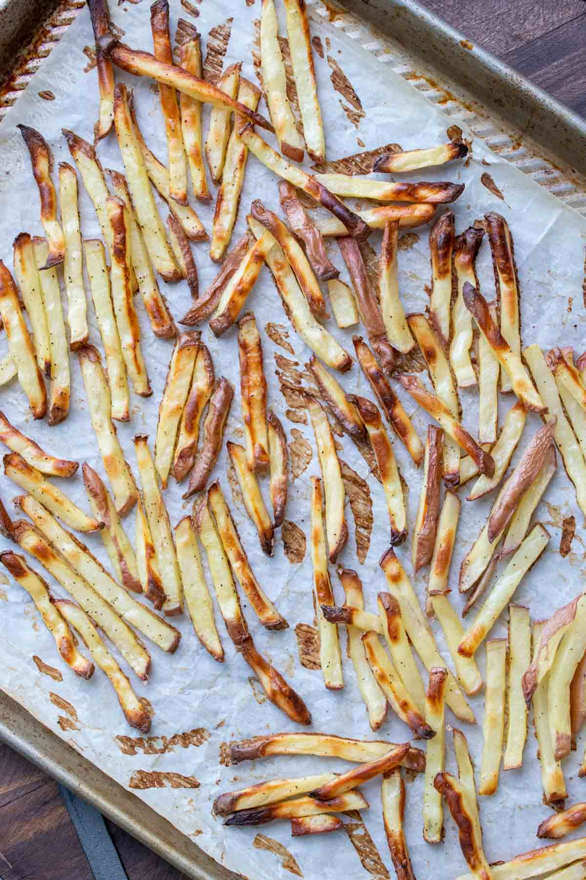 Crispy baked french fries on a parchment lined cookie sheet
