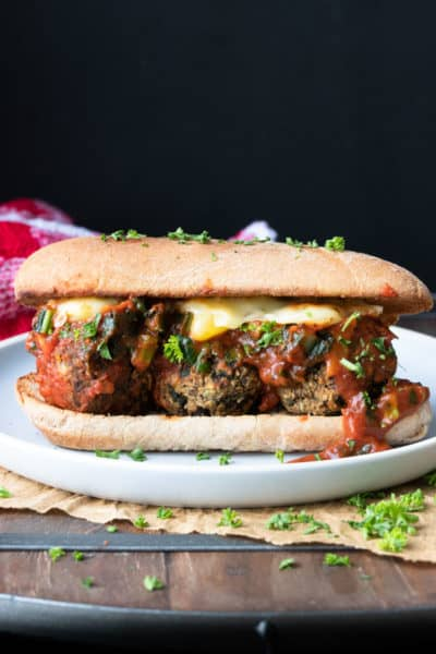 Vegan meatball sub with yellow cheese and marinara on a white plate