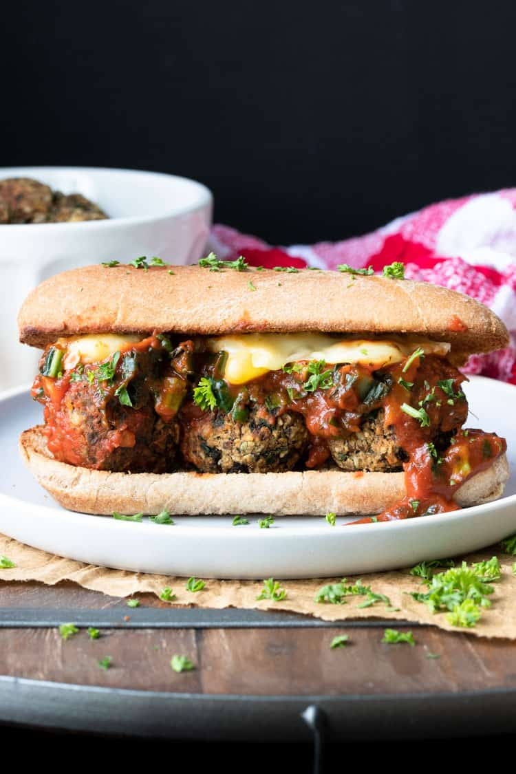 Cheese and marinara over vegan meatballs in a sub sandwich